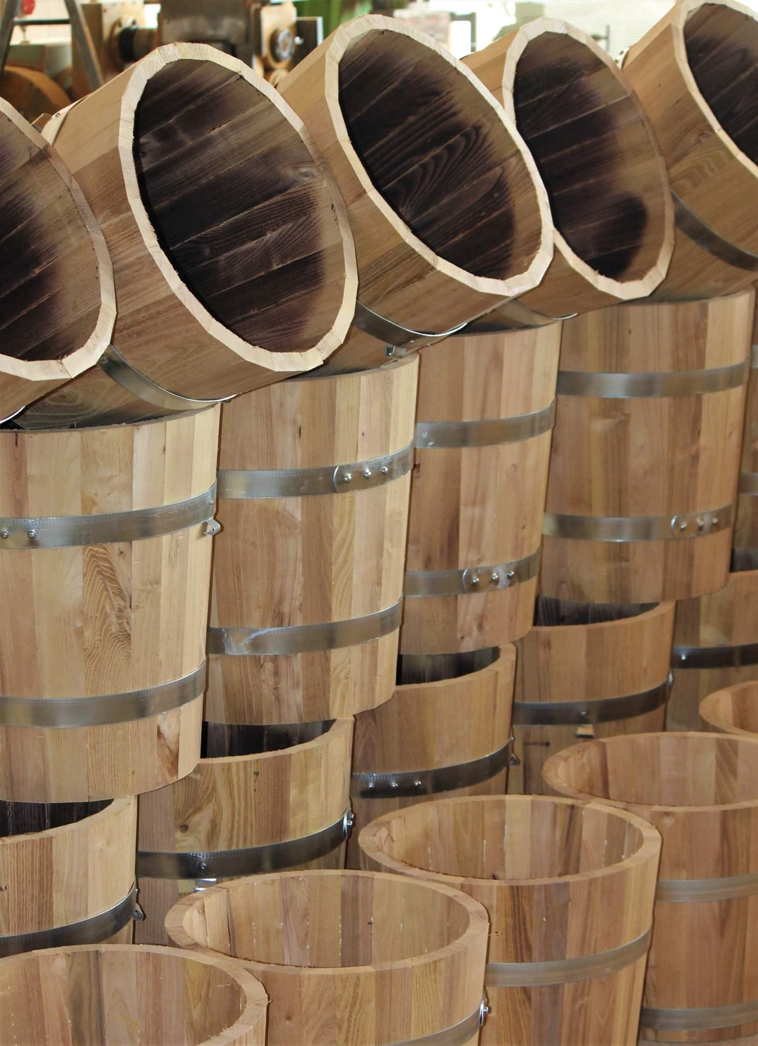 Fertige Pflanzkübel-Rohlinge warten auf die Feuerbehandlung der Innenseite, auf Schliff und Ölen sowie die Montage der Bogenfüsse.